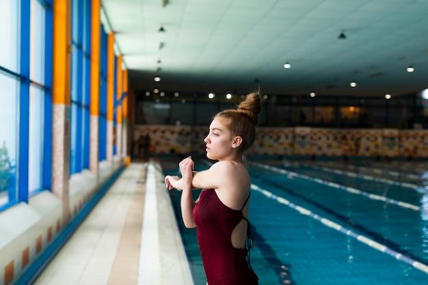 Frau im badeanzug dehnt sich mittlerer schuss
