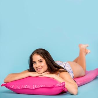 Frau im badeanzug, der auf luftmatratze für das schwimmen und das betrachten der kamera liegt