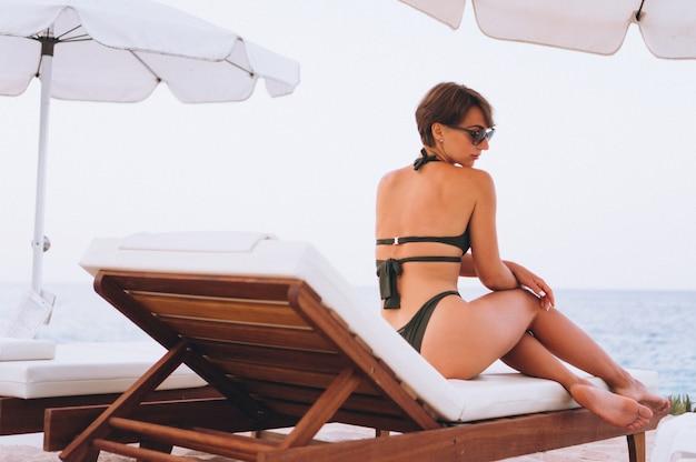 Frau im badeanzug, der durch das meer sich entspannt