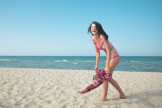 Frau im badeanzug, der spaß auf dem strand hat