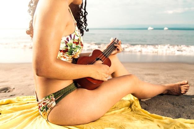 Frau im badeanzug, der ukulele auf strand spielt