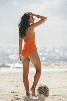 Frau im badeanzug mit wassermelone am strand im freien