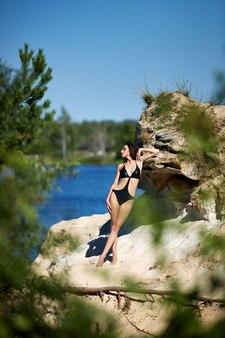 Frau im badeanzug posiert am sommerstrand