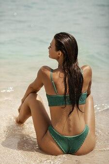 Frau im badeanzug sitzt am strand und schaut auf das meer. rückansicht eines atemberaubenden mädchens Premium Fotos