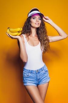 Frau im badeanzug und in blauen kurzen hosen, die banane und aufstellung lokalisiert über gelber szene halten