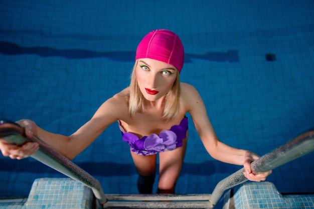 Frau im badeanzug und rosa badehut auf der leiter im schwimmbad