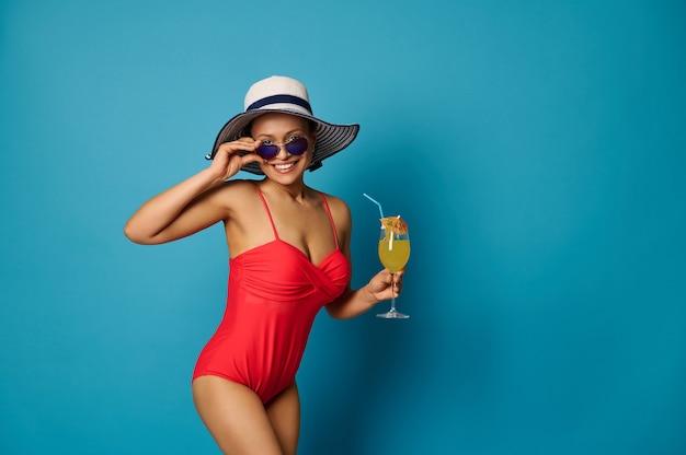 Frau im badeanzug und sommerhut und sonnenbrille mit einem glas saft auf blauem hintergrund