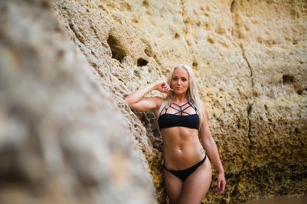 Frau im badeanzug wirft auf sandstrand mit großen steinen im hintergrund auf. schönes gebräuntes mädchen am sandigen ufer des ozeans