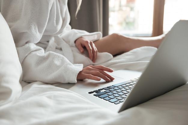 Frau im bademantel auf dem bett und mit laptop