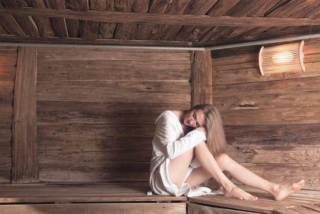 Frau im bademantel, der auf der holzbank sich entspannt an der sauna sitzt