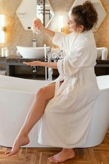 Frau im bademantel, der badewanne vorbereitet