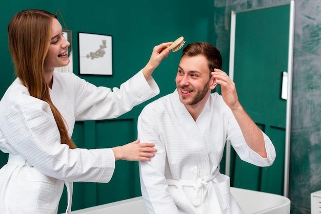 Frau im bademantel, der das haar des mannes bürstet