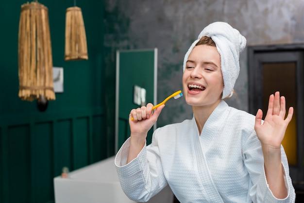 Frau im bademantel, der herum mit zahnbürste spielt