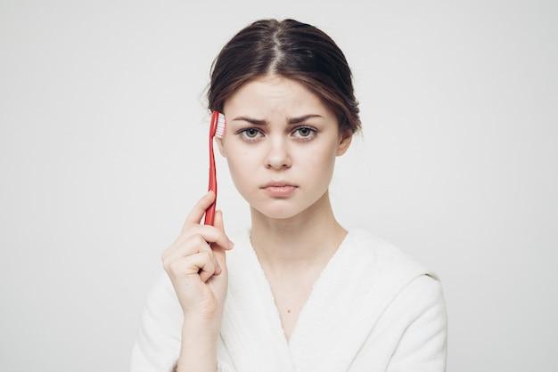 Frau im bademantel, der zähne putzt