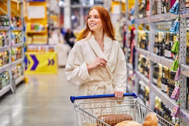 Frau im bademantel, die allein im supermarkt einkauft, produkte auswählt, mit wagen. im marktgang