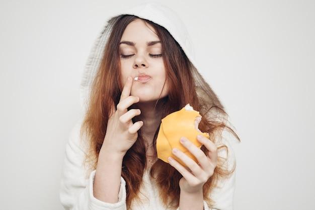 Frau im bademantel, die ein sandwich zu hause isst