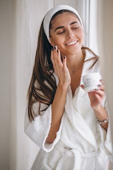 Frau im bademantel gesichtscreme auftragen
