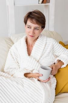 Frau im bademantel hält eine tasse tee