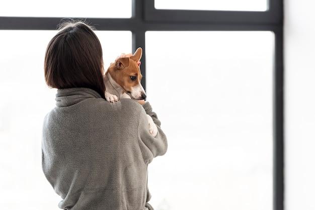 Frau im bademantel hält ihren hund mit kopienraum