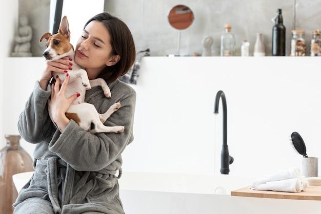 Frau im bademantel hält ihren hund