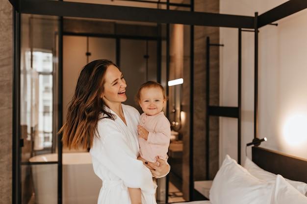 Frau im bademantel hält kleines, lächelndes kind. porträt der mutter mit tochter im schlafzimmer.