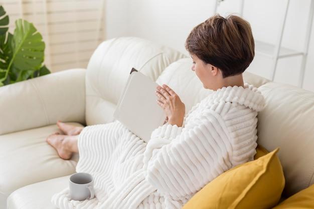 Frau im bademantel liest auf der couch