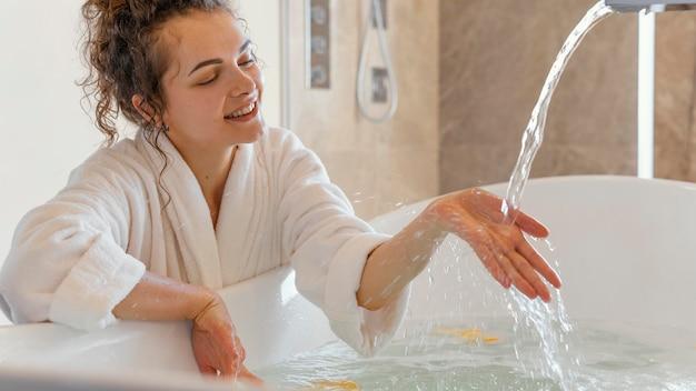 Frau im bademantel mit hand im wasser