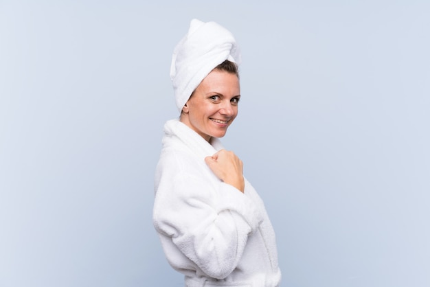Frau im bademantel über der lokalisierten blauen wand, die einen sieg feiert