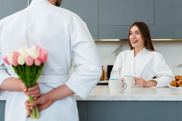 Frau im bademantel überrascht mit blumenstrauß von tulpen vom mann