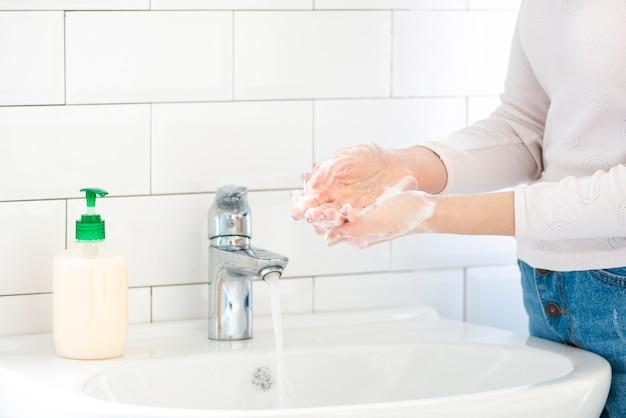 Frau im badezimmer, die ihre hände wäscht