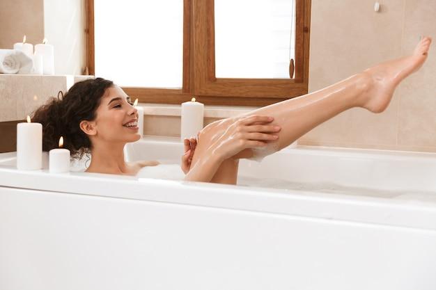 Frau im badezimmer liegt im bad ruhend.