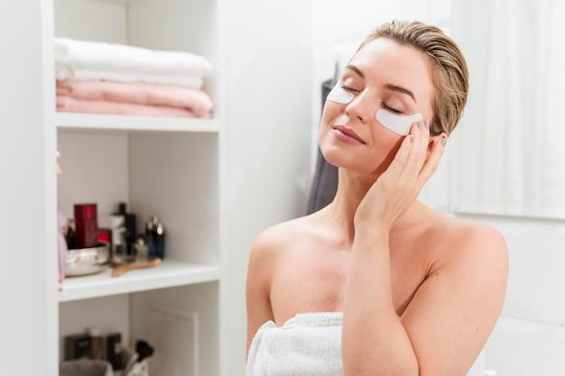 Frau im badezimmer mit behandlung unter augentaschen