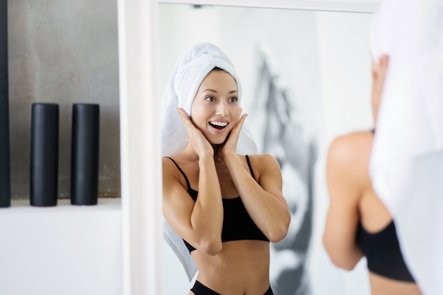 Frau im badezimmer mit einem handtuch auf dem kopf vor einem spiegel.