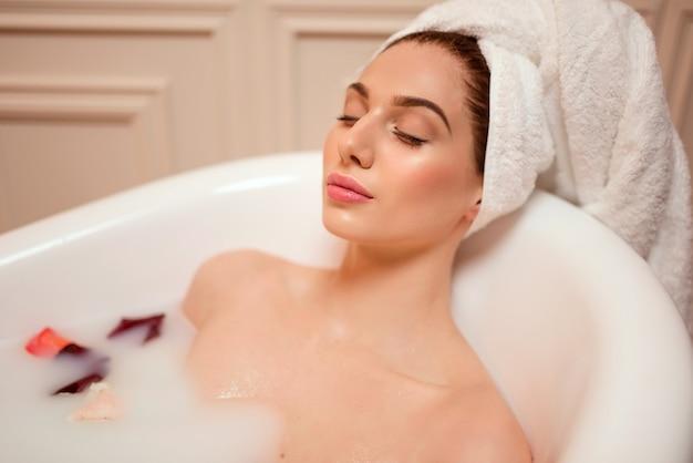 Frau im badezimmer mit rosenblättern