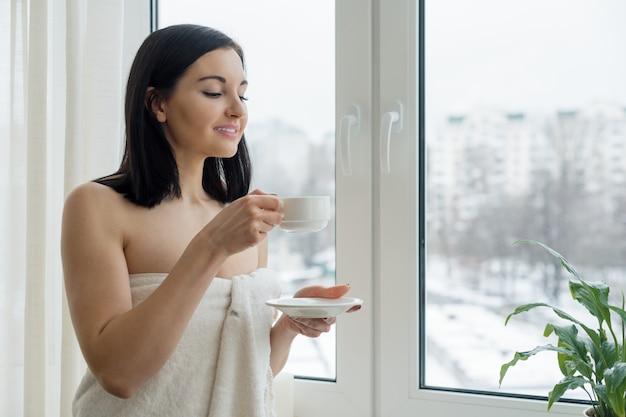Frau im badtuch mit schale frischem kaffee nahe dem fenster