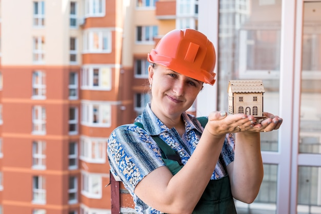 Frau im baumeisterhelm, der hausmodell und schlüssel hält