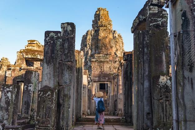 Frau im bayon tempel, der steingesichter betrachtet