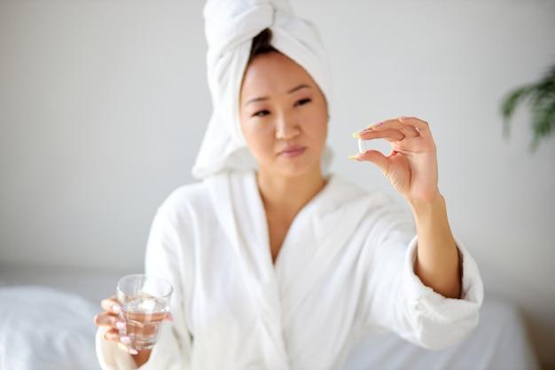 Frau im begriff, eine tablette zu nehmen, pillen in händen zu halten, konzentrieren sich auf pillen. attraktive junge frau, die zu hause auf dem bett sitzt und schmerzmittel mit wasser nimmt.