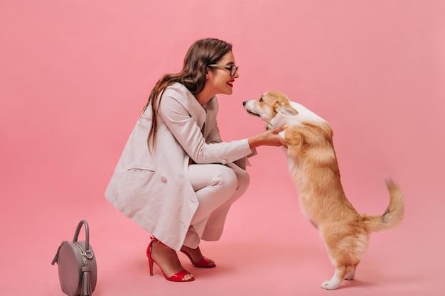Frau im beige anzug spielt mit hund auf rosa hintergrund. nettes schönes mädchen mit brille und roten absätzen schaut auf corgi und lächelt.