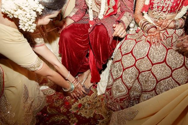 Frau im beige indischen kleid biegt zu den füßen von hochzeitspaaren