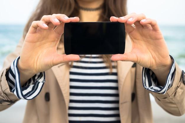 Frau im beigen mantel zeigt den smartphone-bildschirm am strand