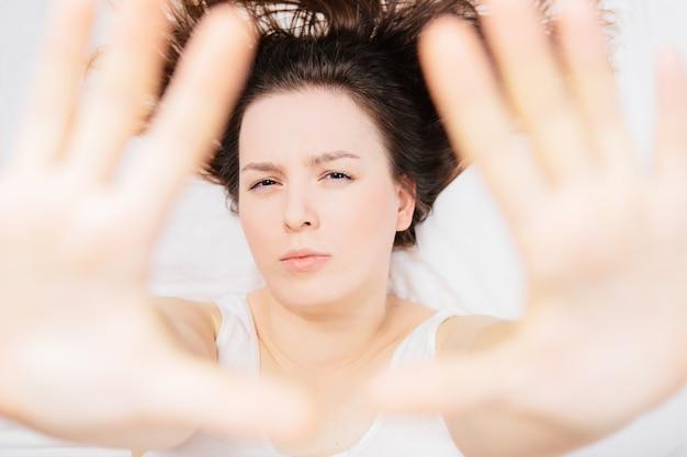 Frau im bett auf einem weißen laken mit verschiedenen emotionen
