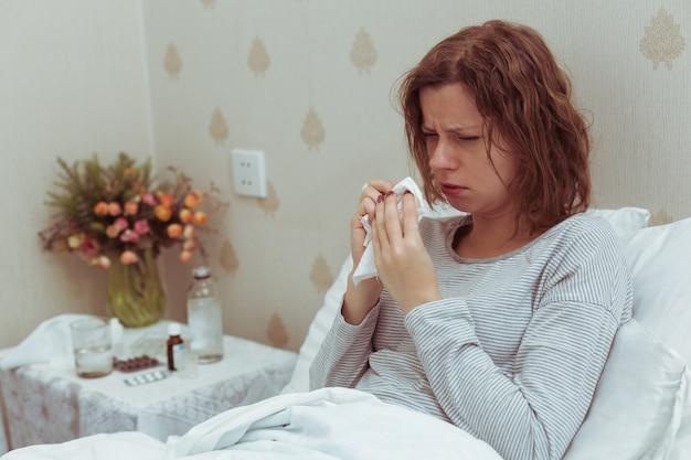 Frau im bett, die hustet und krankhafte symptome von coronavirus hoher temperatur und husten verspürt