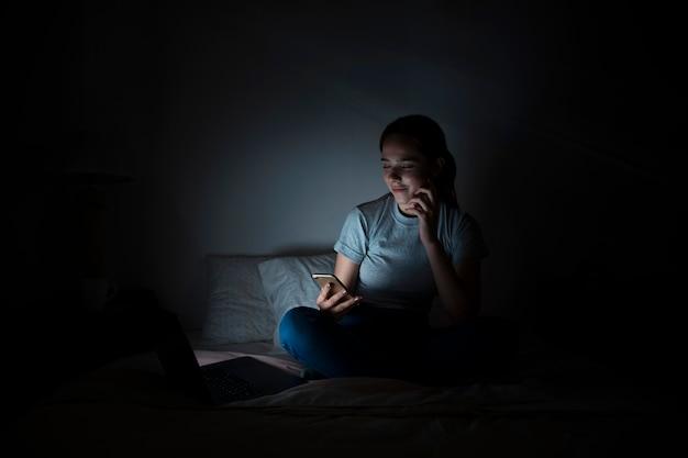 Frau im bett, die smartphone nachts betrachtet