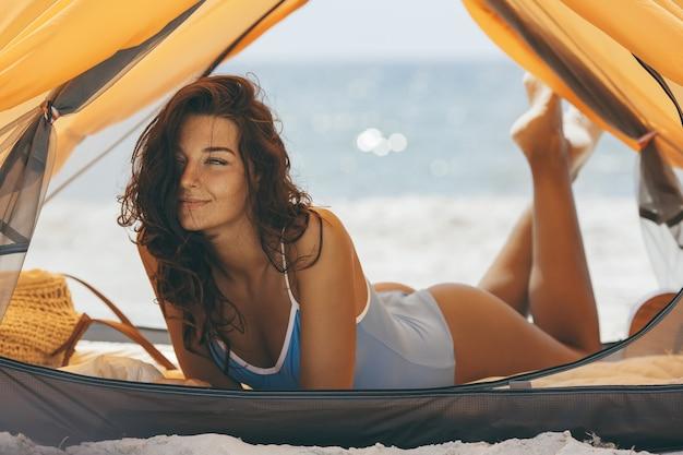 Frau im bikini am strand in einem orangefarbenen zelt