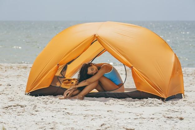 Frau im bikini am strand in einem zelt