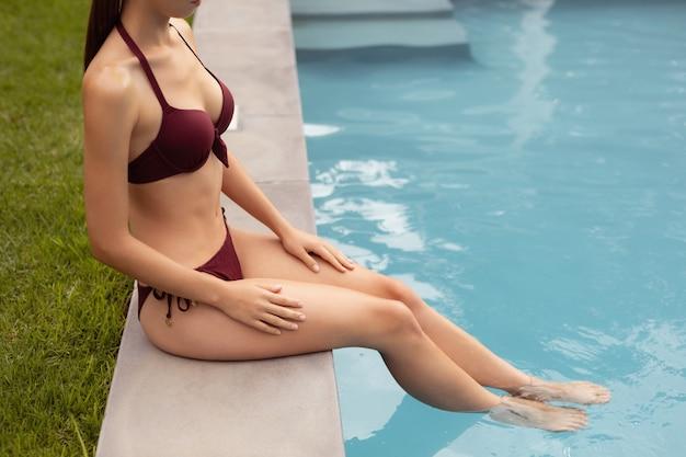 Frau im bikini, der am rand des swimmingpools sitzt