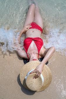 Frau im bikini, der am strand, railay in thailand entspannt.