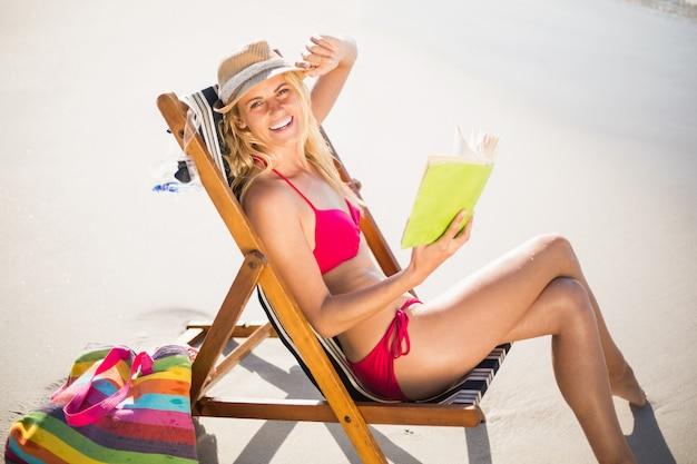 Frau im bikini, der auf lehnsessel und lesebuch sitzt
