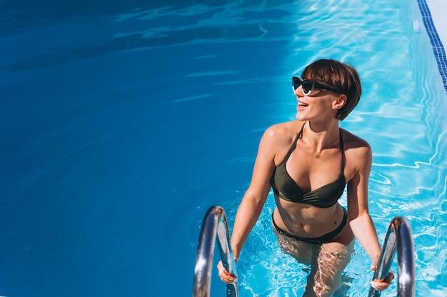 Frau im bikini, der aus das pool herauskommt